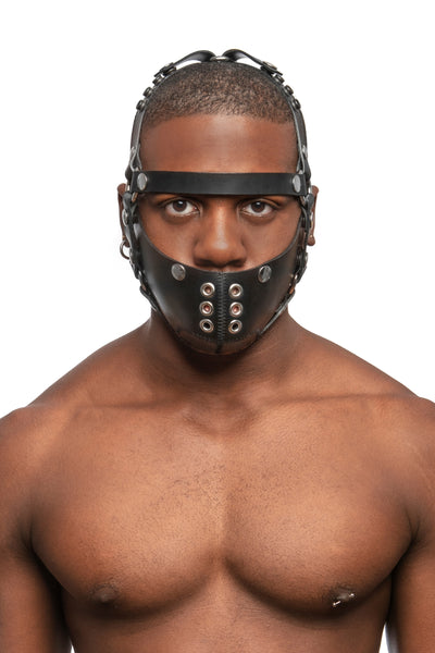 Model wearing black leather head harness and muzzle with stainless steel hardware, front, no nose strap