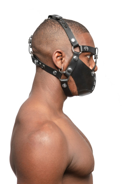 Model wearing black leather head harness and muzzle with stainless steel hardware, side