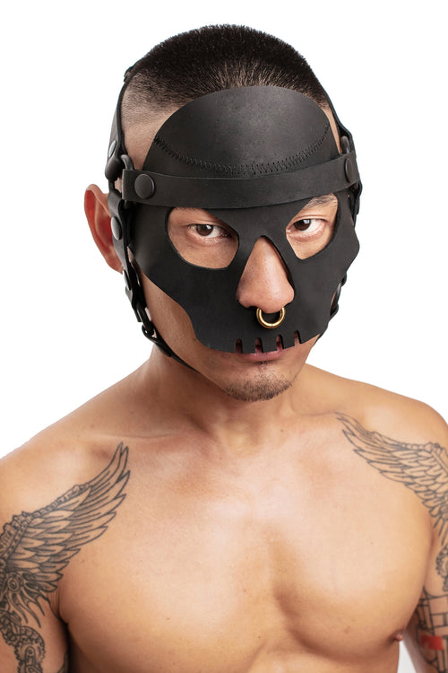 Model wearing black leather head harness and black skull face mask. Front.