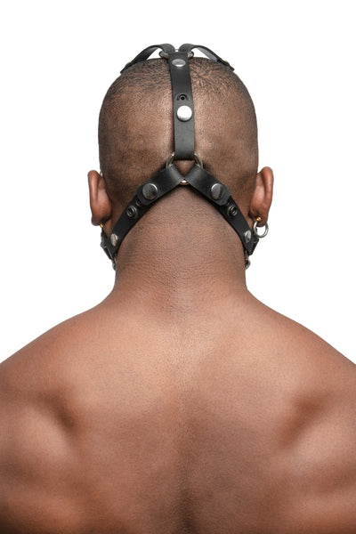 Model wearing black leather head harness with stainless steel hardware, back