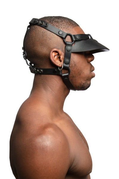 Model wearing black leather head harness and visor with black metal hardware.  Side view.
