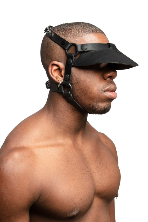 Model wearing black leather head harness and visor with black metal hardware.