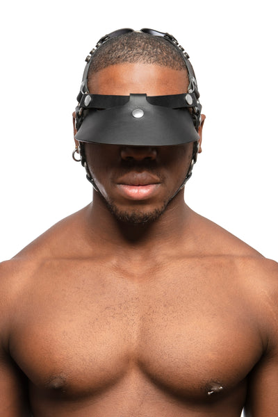 Model wearing black leather head harness and visor with stainless steel hardware. Front view.