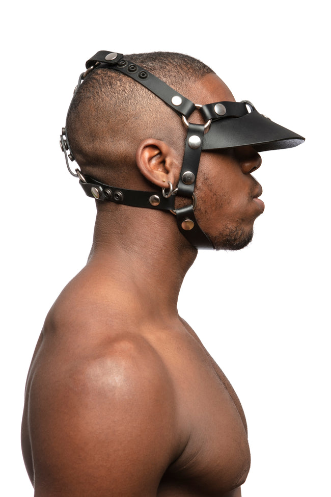 Model wearing black leather head harness and visor with stainless steel hardware. Side view.