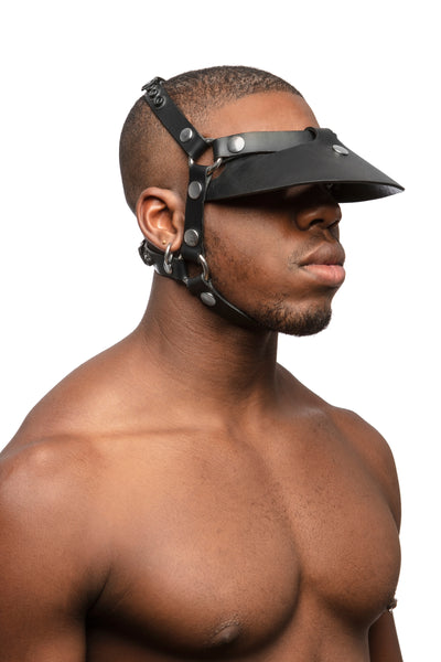Model wearing black leather head harness and visor with stainless steel hardware.