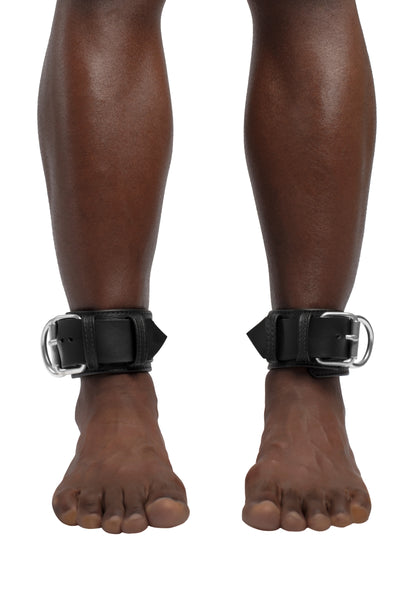 Model wearing black and stainless steel leather ankle restraints