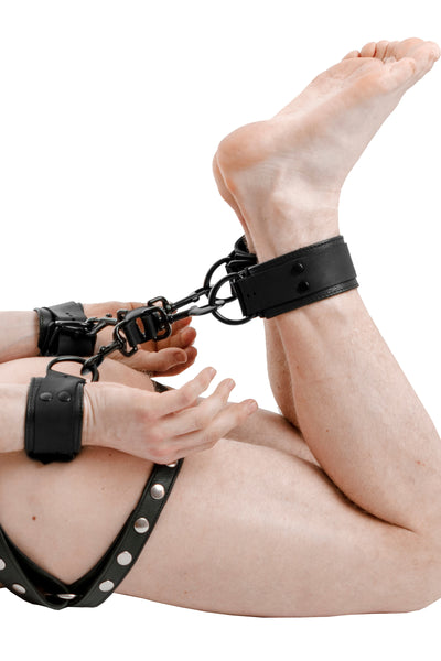 Model wearing a black leather wrist and ankle restraints set