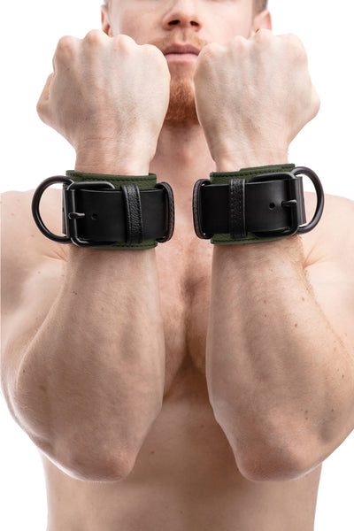 Model wearing black and army green leather wrist restraints