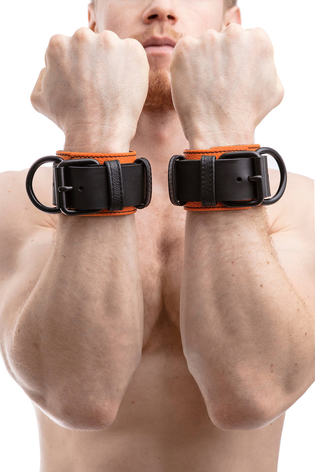 Model wearing orange and black leather wrist restraints