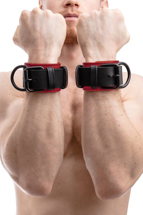 Model wearing black and red leather wrist restraints