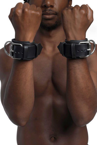 Model wearing black and stainless steel leather wrist restraints