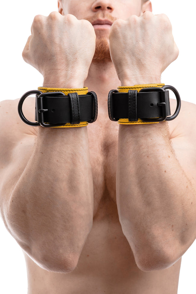 Model wearing black and yellow leather wrist restraints