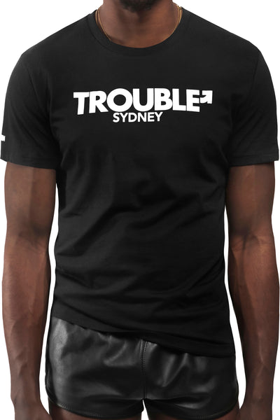 "Model wearing black ""TROUBLE SYDNEY"" t-shirt. Front view."