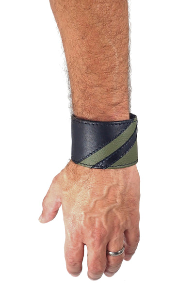 Model wearing a black leather wristband with army green leather chevron detailing