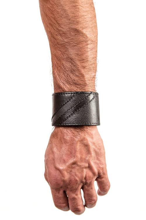 Model wearing a black leather wristband with matt black leather chevron detailing