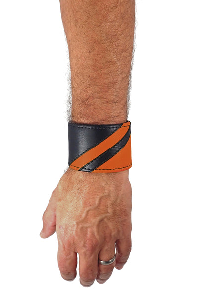 Model wearing a black leather wristband with orange leather chevron detailing