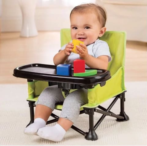 a baby sitting in a high chair eating a banana