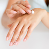Female rubbing Pure Home Body Hand, Face and Body cream on hands