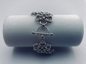 Closeup of working clasp on seaXwolf handmade fine jewelry signature HexaFleur Undulating, solid sterling silver chain mail flower bracelet.