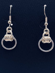 Seaxwolf handmade sterling silver four rings and small hoop earrings.