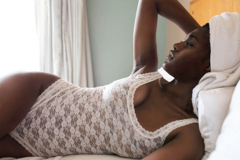 woman wearing white lace body suit laying on bed