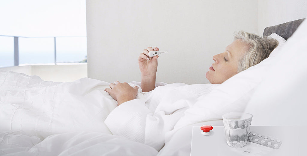 Red Fibaro the button on night stand next to sick elderly lady in bed