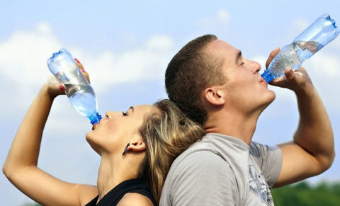 Healthy couple drinking from a water bottle