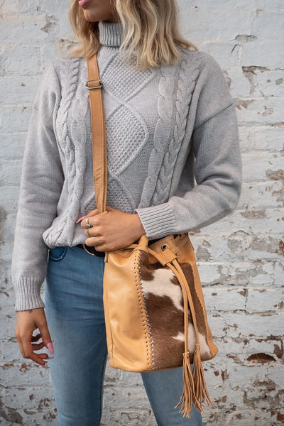 Tan leather bucket bag with cowhide front detail