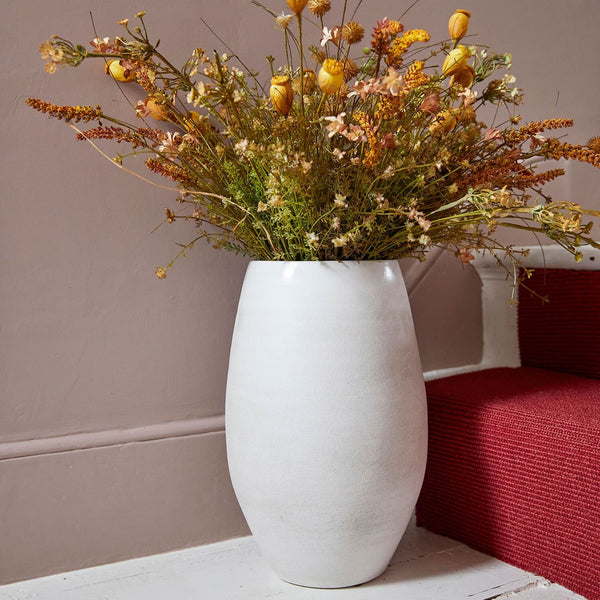 Off white ceramic vase with dried flowers