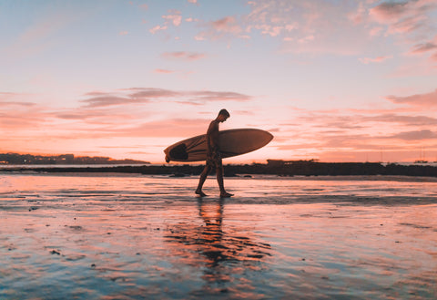 Man walking along the beach with Surf Board