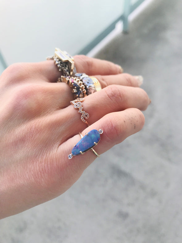 hand with several stacked rings and an opal ring on pink finger