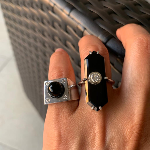 Onyx statement rings on hand resting on a woven textured chair