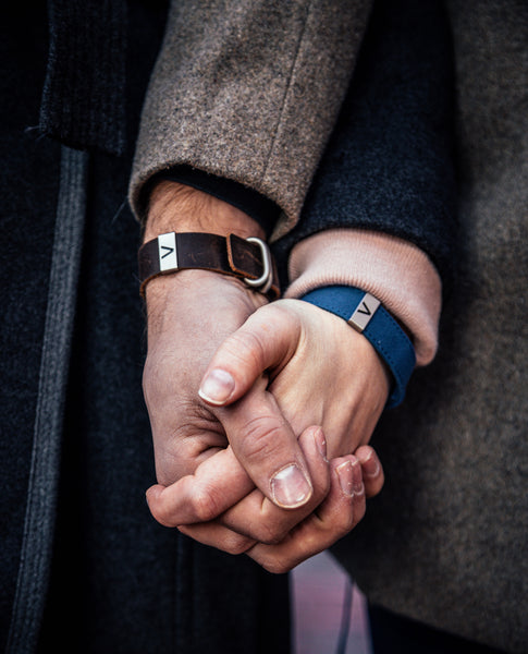 Two people holding hands, wearing a radtagz bracelet in blue canvas and black woven nylon