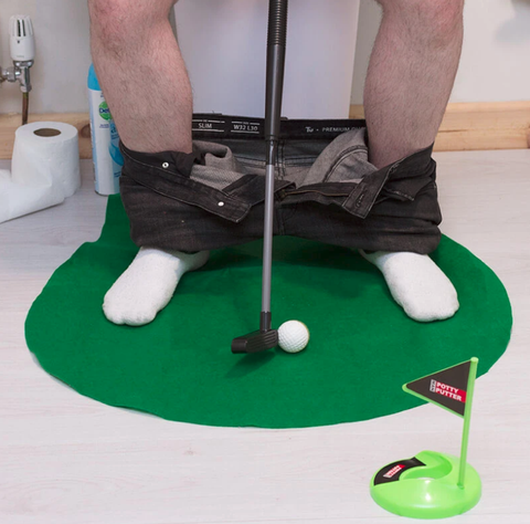 man sitting on toilet with mini putting green
