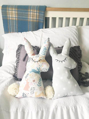 two bunny cushions on the bed