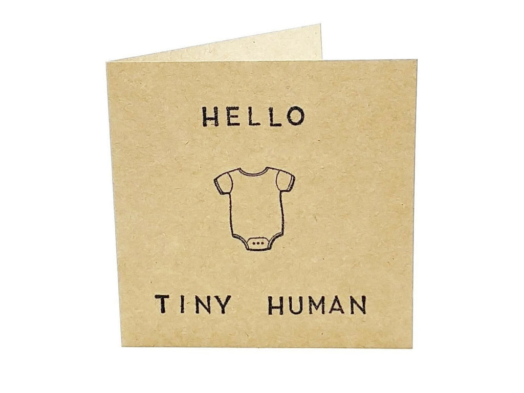 square brown gender neutral craft paper card saying hello tiny human with a babygrow