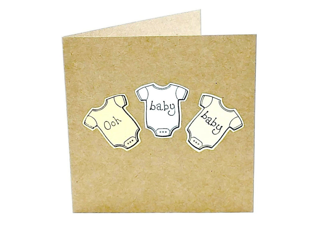 square brown gender neutral craft paper card with 3 baby grow in pastel colours
