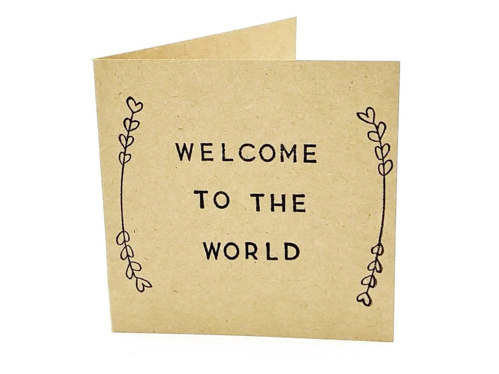 gender neutral square brown craft paper card saying welcome to the world
