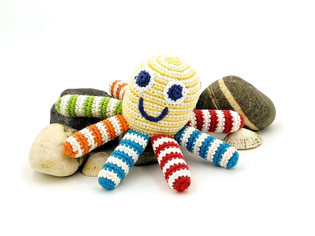 octopus gender neutral soft toy with different colour bright stripey tentacles sitting on rocks