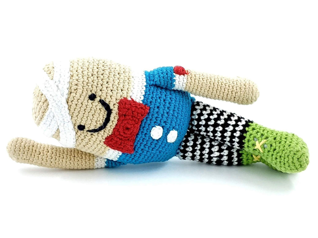 egg soft toy with bandaged head, blue jumper, red bow tie, black and white leggings and green boots lying down, gender neutral toy