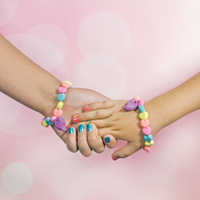 Girls holding hands with OOLY BFF Scented Eraser Bracelets