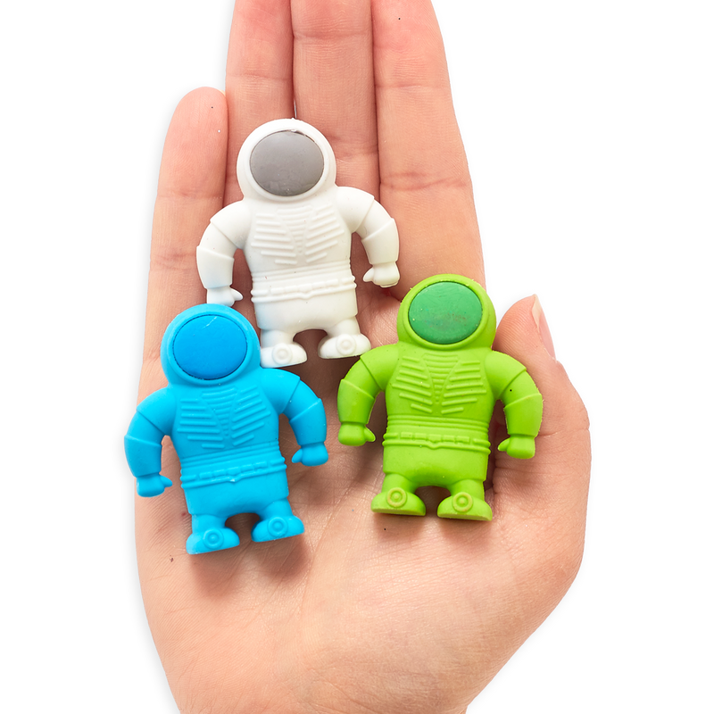 Blue, white and green astronaut erasers in the palm of a hand