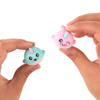 Hands holding up pink and turquoise narwhal erasers