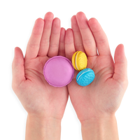 Three Le Macaron Patisserie Scented Erasers in persons hands