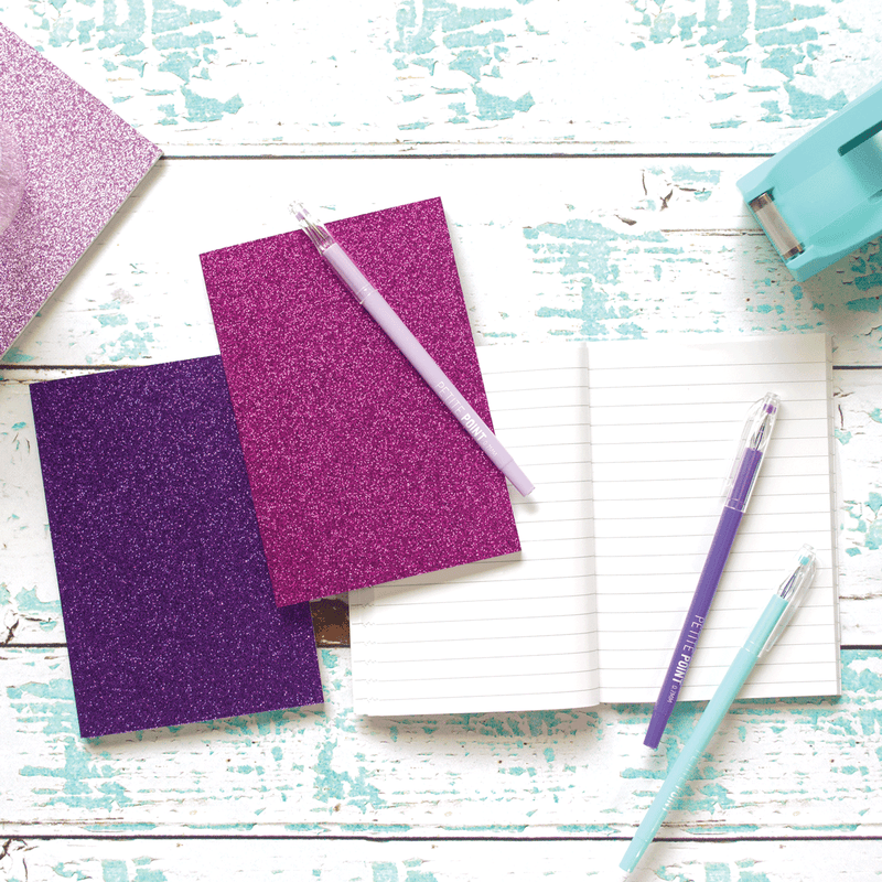 Pink Glamtastic glitter notebooks shown on a desk open with writing and a pom pom pen.
