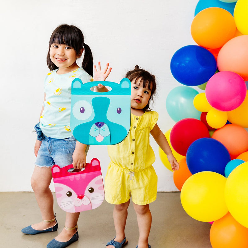 Happy girls holding dog and cat Carry Along Sketchbooks next to colorful balloons