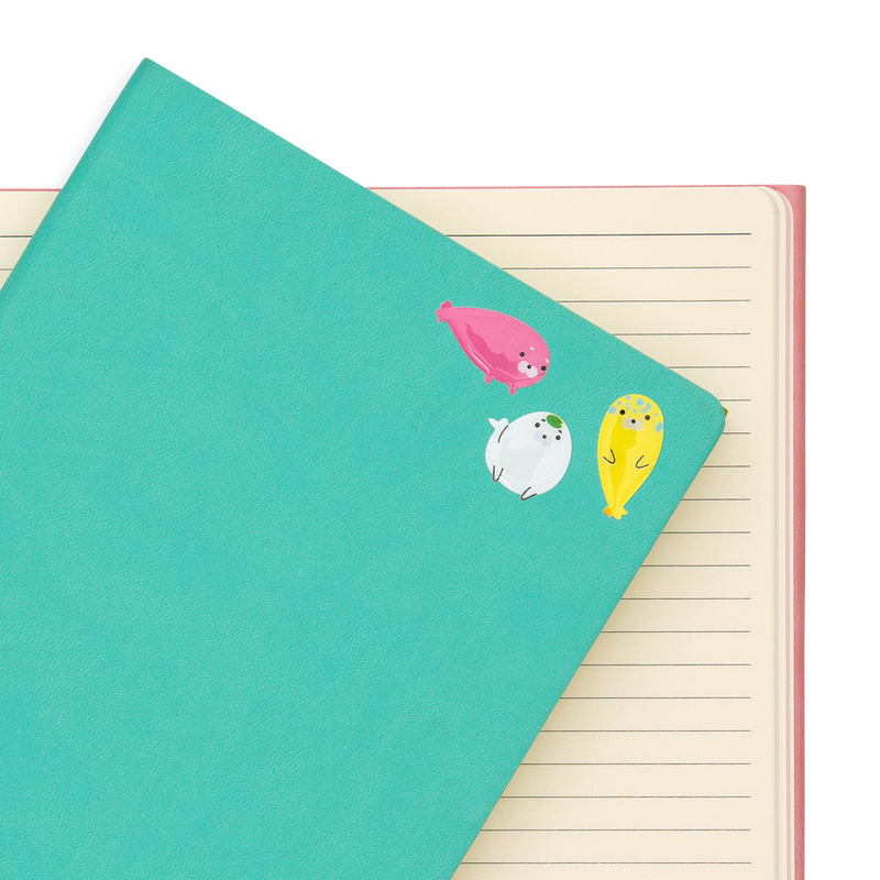 Some Itsy Bitsy - Slippery Seals mini stickers on a green notebook.