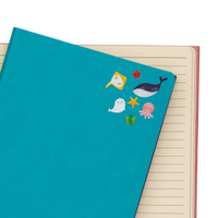 Some of the Itsy Bitsy - Marine Friends mini stickers on a teal notebook.