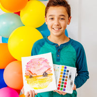 Smiling boy standing in front of balloons and holding up watercolor artwork and chroma blends travel watercolor palette