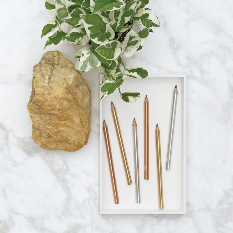 Modern Graphite Pencils on marble table with rock and plant